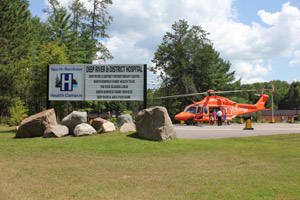 Hosptial signage with helicopter in background