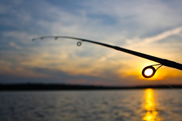 Fishing rod at sunset over river